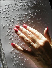 shows a hand reading braille
