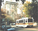 shows light rail vehicle with apartment building in the back